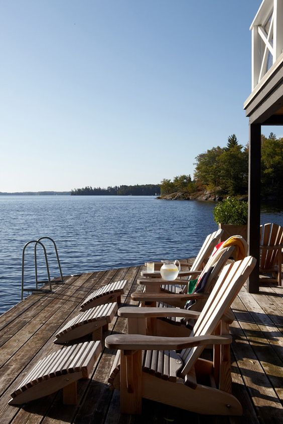 row of muskoka chairs on cottage dock with lemonade pitcher and glass